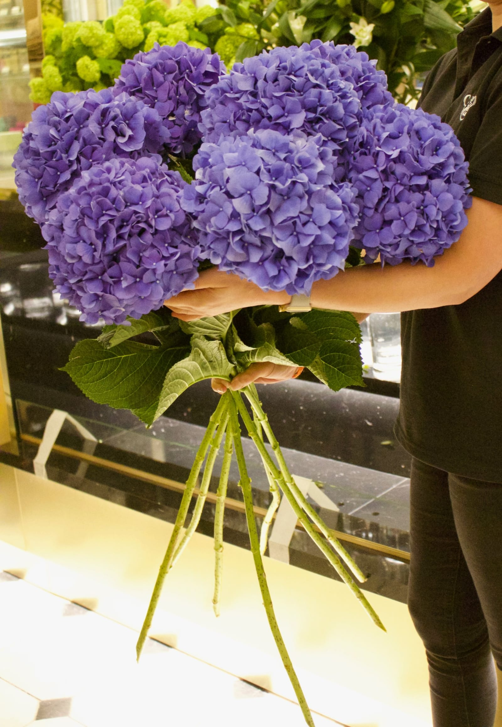 Purple flowers held by staff at Harrods in London.